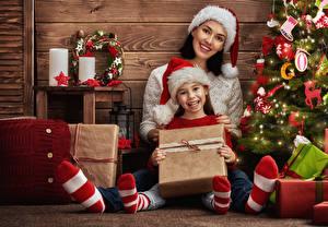 Обои Праздники Рождество Доски Новогодняя ёлка Девочки Вдвоем Шапки Улыбка Подарки Дети