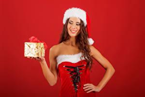 Картинки Рождество Шатенка Униформа Улыбка Шапки Подарки Красный фон Девушки
