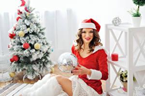 Фото Рождество Шатенка Шапки Униформа Улыбка Новогодняя ёлка Шар Девушки