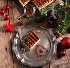 Картинки Новый год Пирожное Сладости Доски Тарелка Вилка столовая Стакан Какао порошок Шарики Шишки Пища