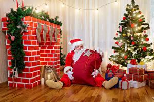 Картинка Новый год Новогодняя ёлка Подарки Санта-Клаус Ветки Фонарь Гирлянда Сидящие Камин