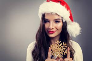 Картинка Рождество Пальцы Серый фон Брюнетка Шапки Улыбка Снежинки Лицо Девушки
