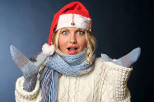 Фото Новый год Сером фоне Блондинка Эмоции изумление Шапки Шарф Рукавицы молодая женщина