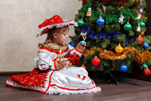 Фото Рождество Праздники Новогодняя ёлка Девочки Платье Сидящие Шляпа Шар Ребёнок