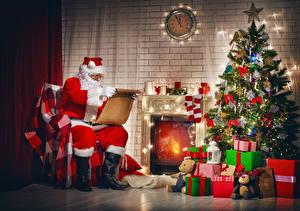 Картинка Новый год Праздники Часы Свечи Новогодняя ёлка Подарки Санта-Клаус Сидя Носки
