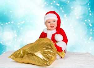 Фото Новый год Праздники Младенцы Улыбается Подарки Шапки Ребёнок