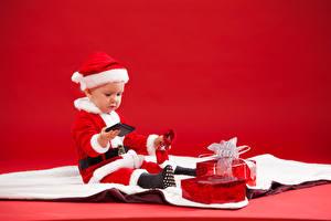 Картинки Рождество Праздники Грудной ребёнок Униформа Мальчики Подарки Телефон Красный фон Ребёнок