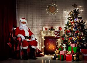 Фото Новый год Интерьер Часы Свечи Стенка Елка Подарки Санта-Клаус Сидит Камин