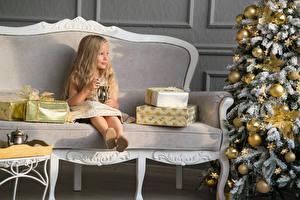 Обои Рождество Девочка Диван Сидит Подарок Новогодняя ёлка Шар ребёнок