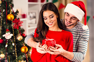 Фото Рождество Мужчины Любовь 2 Шатенка Шапки Подарки Улыбка Руки Девушки