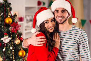 Фотография Новый год Мужчины Две Шапка Улыбка Руки Радость молодые женщины