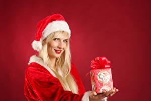 Фотографии Рождество Красный фон Блондинка Улыбка Подарки Шапки Девушки