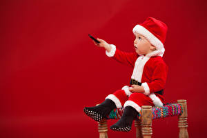 Фото Рождество Красный фон Мальчики Униформа Шапки Сидящие Ребёнок