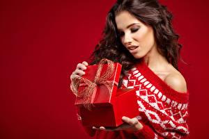 Картинки Рождество Красный фон Шатенка Подарки Коробка Девушки