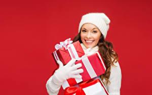 Картинка Новый год Красном фоне Шатенка Улыбка Подарков Шапка Перчатках Девушки