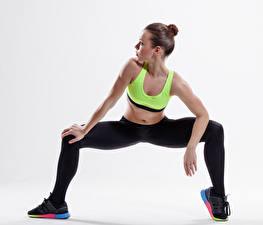 Картинка Фитнес Белом фоне Шатенка Кроссовки Рука Ноги молодые женщины Спорт