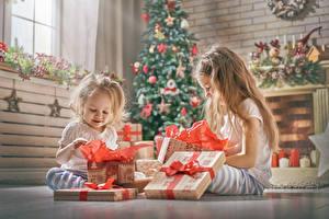 Фотографии Праздники Новый год Вдвоем Девочки Подарки Сидящие Ребёнок