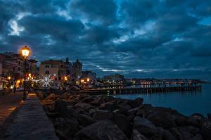 Картинка Италия Здания Побережье Камни Небо Вечер Уличные фонари Ischia Ponte