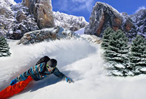 Картинки Сноуборд Зима Мужчины Скала Снег Шлем Ель Спорт