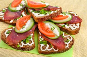 Фотографии Бутерброды Хлеб Огурцы Томаты Колбаса Цветной фон