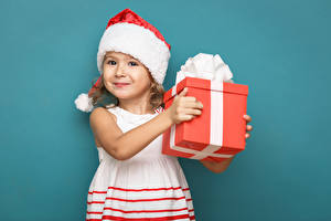 Картинки Рождество Цветной фон Девочки Шапки Подарки Улыбка Платье Дети