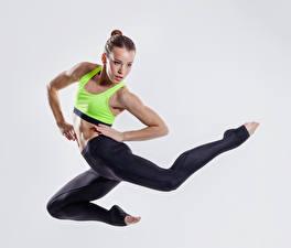 Обои Фитнес Серый фон Шатенка Прыжок Рука Ног Девушки Спорт