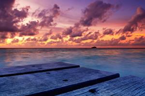 Фото Мальдивы Тропики Море Рассветы и закаты Небо Пирсы Облака