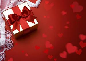 Фото День всех влюблённых Красный фон Подарки Бантик Сердечко