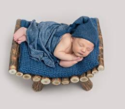 Фото Цветной фон Грудной ребёнок Спит Шапки Дети
