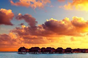 Картинка Мальдивы Тропики Рассветы и закаты Небо Бунгало Облака