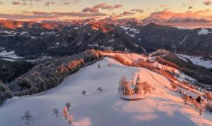 Картинки Словения Зимние Горы Леса Церковь Снег Альпы Skofja Loka Природа