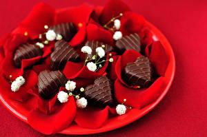 Фотографии День всех влюблённых Сладости Конфеты Шоколад Красный фон Сердечко Лепестки Пища