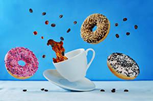 Фото Пончики Кофе Цветной фон Чашка Зерна Пища