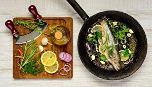Фото Рыба Специи Лимоны Чеснок Лук репчатый Укроп Разделочная доска Сковородка Продукты питания