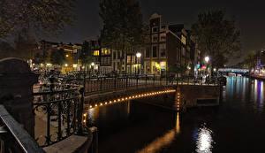 Картинка Нидерланды Амстердам Здания Мосты Водный канал Ночь Уличные фонари Велосипеды Города