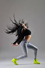 Фотографии Серый фон Шатенка Танцует Джинсы Наушники Девушки