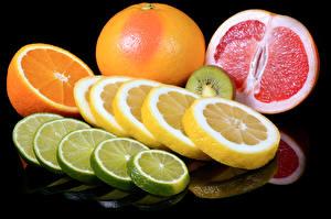 Фото Цитрусовые Лимоны Апельсин Грейпфрут Черный фон Нарезанные продукты
