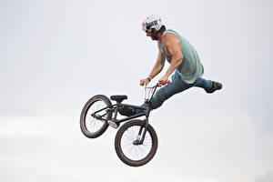 Фотографии Мужчины Серый фон Велосипед Шлем Прыжок Спорт