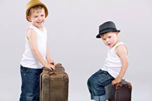 Картинки Серый фон Мальчики Двое Улыбка Шляпа Чемодан Дети