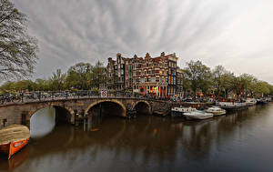 Фото Нидерланды Амстердам Здания Мосты Пирсы Вечер Корабли Речные суда Водный канал