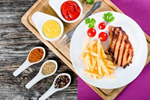 Фотографии Вторые блюда Мясные продукты Картофель фри Помидоры Специи Доски Тарелка Кетчуп Продукты питания