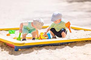 Фотографии Игрушки Мальчик Две Песок Играет ребёнок