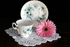 Фотографии Натюрморт Герберы Черный фон Чашка Тарелка Розовый Цветы