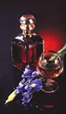 Картинки Натюрморт Ирисы Виски Черный фон Бутылка Бокалы Пища
