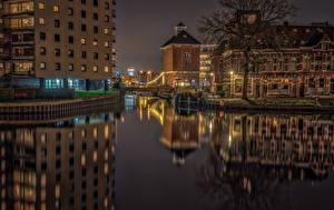Картинка Нидерланды Дома Реки Мосты Ночь Уличные фонари Groningen