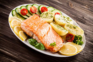 Фотографии Морепродукты Рыба Картошка Овощи Лососи Доски Тарелке Продукты питания