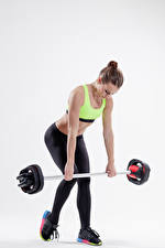 Картинки Фитнес Серый фон Шатенка Тренировка Штангой молодые женщины Спорт