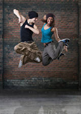 Картинки Мужчины Стенка 2 Танцует В прыжке Счастливый Рука Шапка Девушки