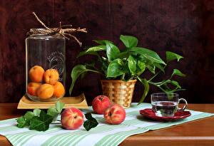 Фото Натюрморт Персики Абрикос Банки Чашка Ветки Продукты питания