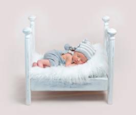 Картинка Цветной фон Кровать Младенцы Спит Шапки Ребёнок